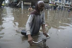 A man wades through a flooded street after a heavy rainfall in Lahore, Pakistan (AP /K.M. Chaudary).