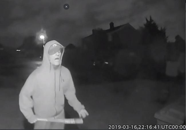CCTV grab issued by Thames Valley Police showing Vincent Fuller swinging a baseball bat outside a neighbours house during a terror attack in Stanwell, Surrey on 16 March.