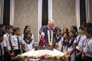 The Prince of Wales cuts a birthday cake alongside school children during a British Asian Trust reception in Mumbai, on day two of the royal visit to India.  Victoria Jones/PA