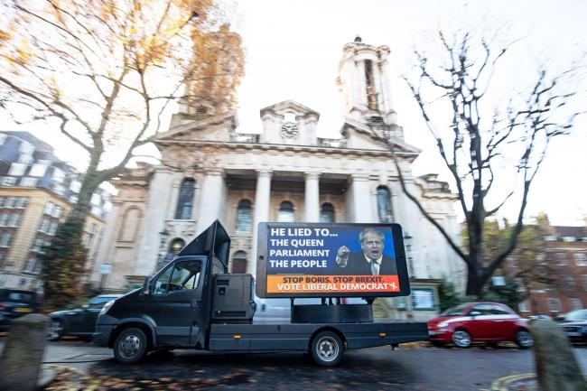 One of four poster vans that are set to tour Liberal Democrat/Conservative marginal seats at their unveiling in Smith Square, Westminster. (Aaron Chown/PA)