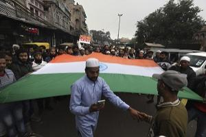 Indians carry a giant flag during a protest against a new Citizenship law, after Friday prayers in New Delhi, India, Friday, Jan. 17, 2020. Protests against India's citizenship law that excludes Muslim immigrants continue in Indian cities in an unabating strong show of dissent against the Hindu nationalist government of Prime Minister Narendra Modi. (AP Photo/Manish Swarup).