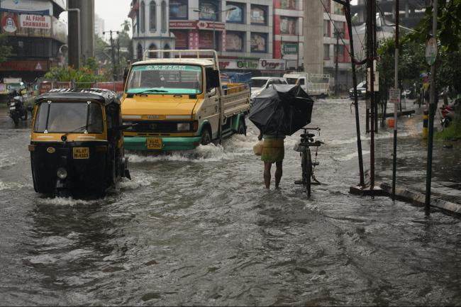 Vehicles move through a waterlogged street during heavy rainfall in Kochi, Kerala state
