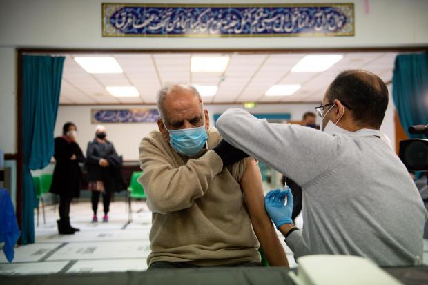 Masud Ahmad, 79, receives an injection of the Oxford/AstraZeneca coronavirus vaccine at the Al Abbas Mosque, Birmingham, which is being used as a covid vaccination centre.