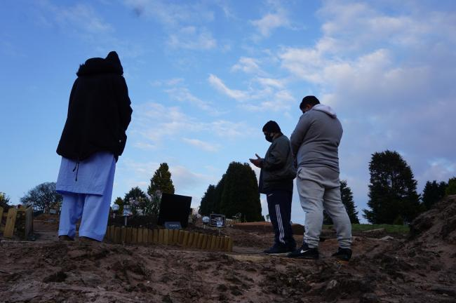 Members of the family pray at  the grave of Musarat Bibi at Pleasington Cemetery Blackburn (Picture LT)