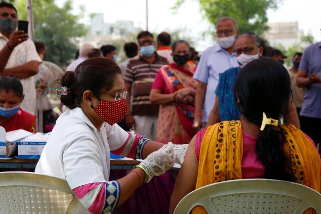 A health worker administers a vaccine in India
