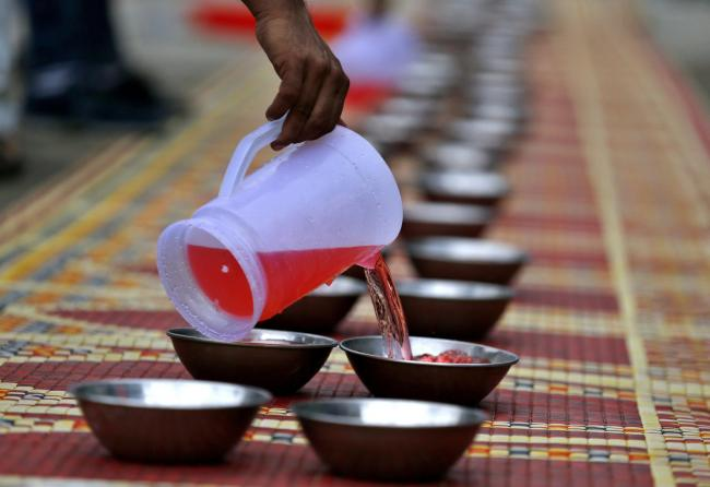 A volunteer fills pots with traditional sweet drink to be distributed among people for breaking their fast during the holy fasting month of Ramadan, at a free food distributing point in Rawalpindi, Pakistan (AP/Naveed).