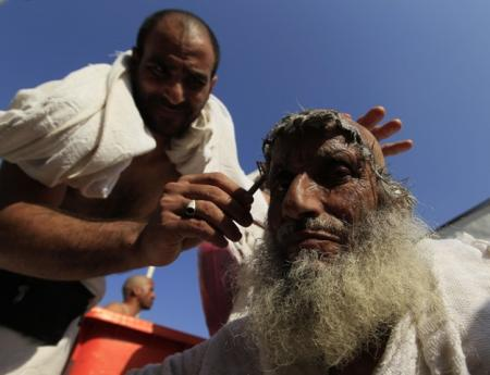 A Muslim pilgrim has his head shaved, after throwing pebbles at a stone