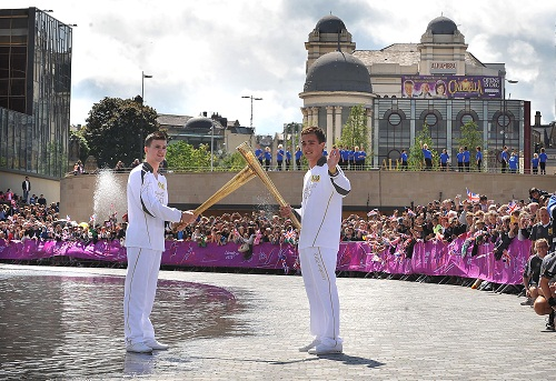 Runner Thomas Stokes hands over the flame to swimmer Jamie Brown  in front of a huge crowd in Bradford's City Park