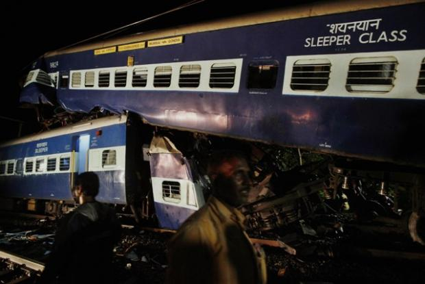 Indian rescue workers and other people work near the mangled wreckage of a train collision in Kasara, India