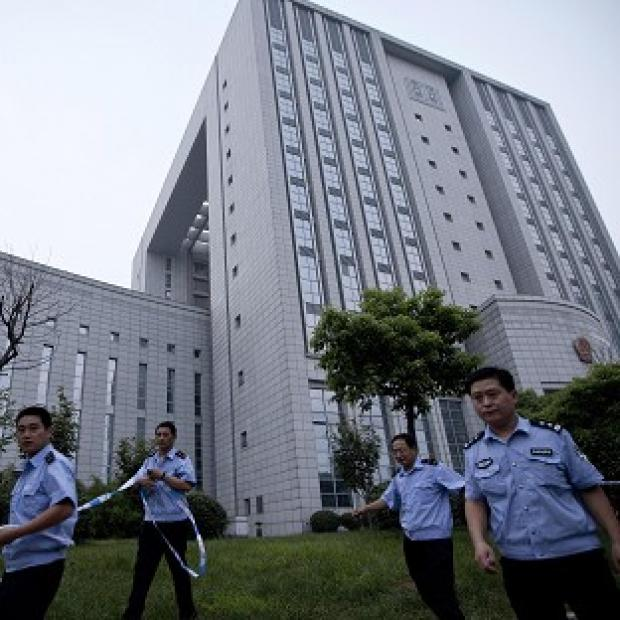 Asian Image: Police officers place a cordon around the Hefei City Intermediate People's Court for the murder trial of Gu Kailai (AP/Andy Wong)