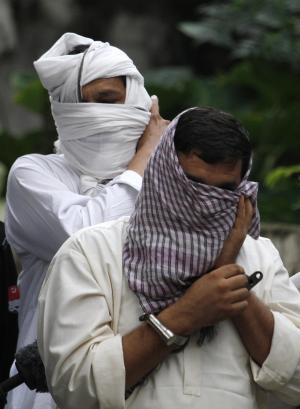 Asian Image: Ex-husband Muhammad Shakeel, front, and father Muhammad Shahid of slain British-Pakistani woman Samia Shahid are escorted by Pakistani police officers to a court in Jhelum in eastern Pakistan. Pakistani police have submitted initial charges to a court against the two men for holding their trial for killing her, court officials and a defense lawyer said. (AP /Anjum Naveed)