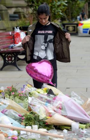 Asian Image: Iqra Saied, 13, wears an Ariana Grande t-shirt as she looks at flowers outside Manchester Town Hall in Manchester after a suicide bomber killed 22 people leaving a pop concert at Manchester Arena on Monday night.