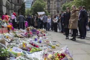 People look at flowers outside the Town Hall in Albert Square, Manchester