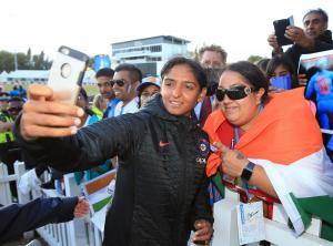 Asian Image: India Women's Harmanpreet Kaur takes a picture with a fan after victory in the ICC Women's World Cup Semi Final match at The County Ground, Derby.  India are set to play England in the final on Sunday. (Nick Potts/PA )