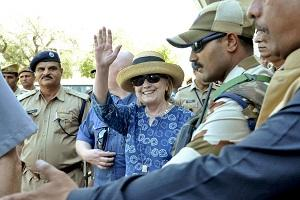 Former U.S. Secretary of State Hillary Clinton, center, waves as she comes out of the Jodhpur airport upoon her arrival in Jodhpur, Rajasthan state, India, Tuesday, March 13, 2018. (AP/Sunil Verma).