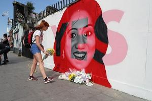 A woman lays flowers next to a mural of Savita Halappanavar in Dublin, as Ireland goes to the polls to vote in the referendum on the 8th Amendment of the Irish Constitution. Friday May 25, 2018. (Niall Carson/PA)