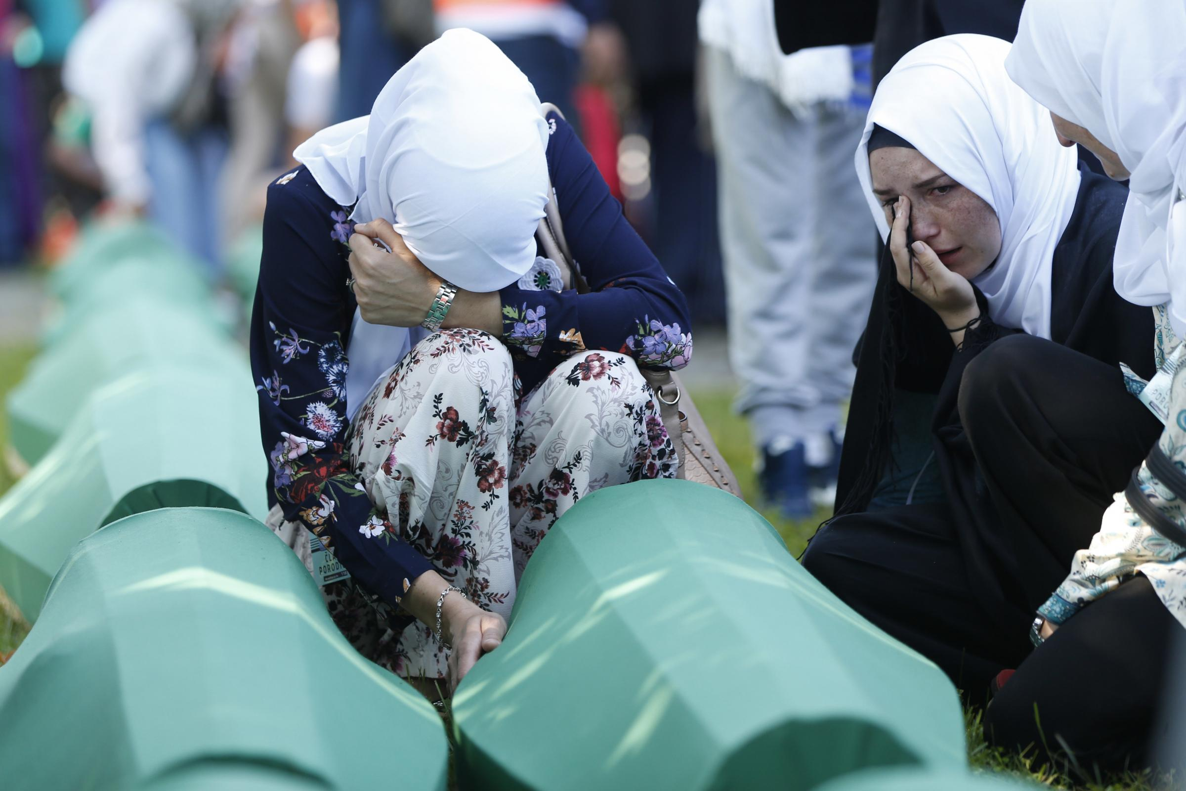 Women grieve over the coffins