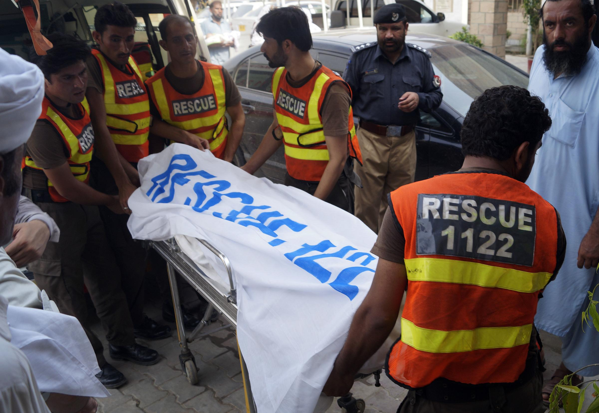 Rescue workers move the body of Ikramullah Gandapur, a candidate from opposition leader Imran Khan's party, who was killed in the suicide bombing, for postmortem at a hospital in Dera Ismail Khan, Pakistan, Sunday, July 22, 2018.