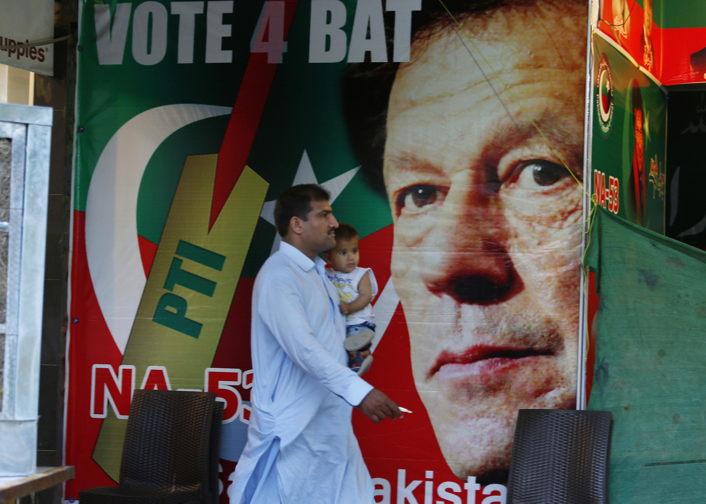 A man walks past a poster of Imran Khan, head of Pakistan Tehreek-e-Insaf party, at a market in Islamabad, Pakistan, Saturday, July 28, 2018.