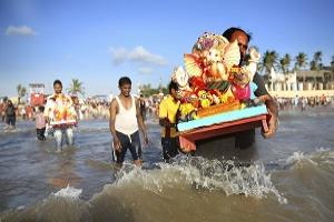 Devotees carry a Ganesha idol into the Arabian sea for immersion during the Ten days long Ganesha festival in Mumbai, India. (AP/Rafiq Maqbool).