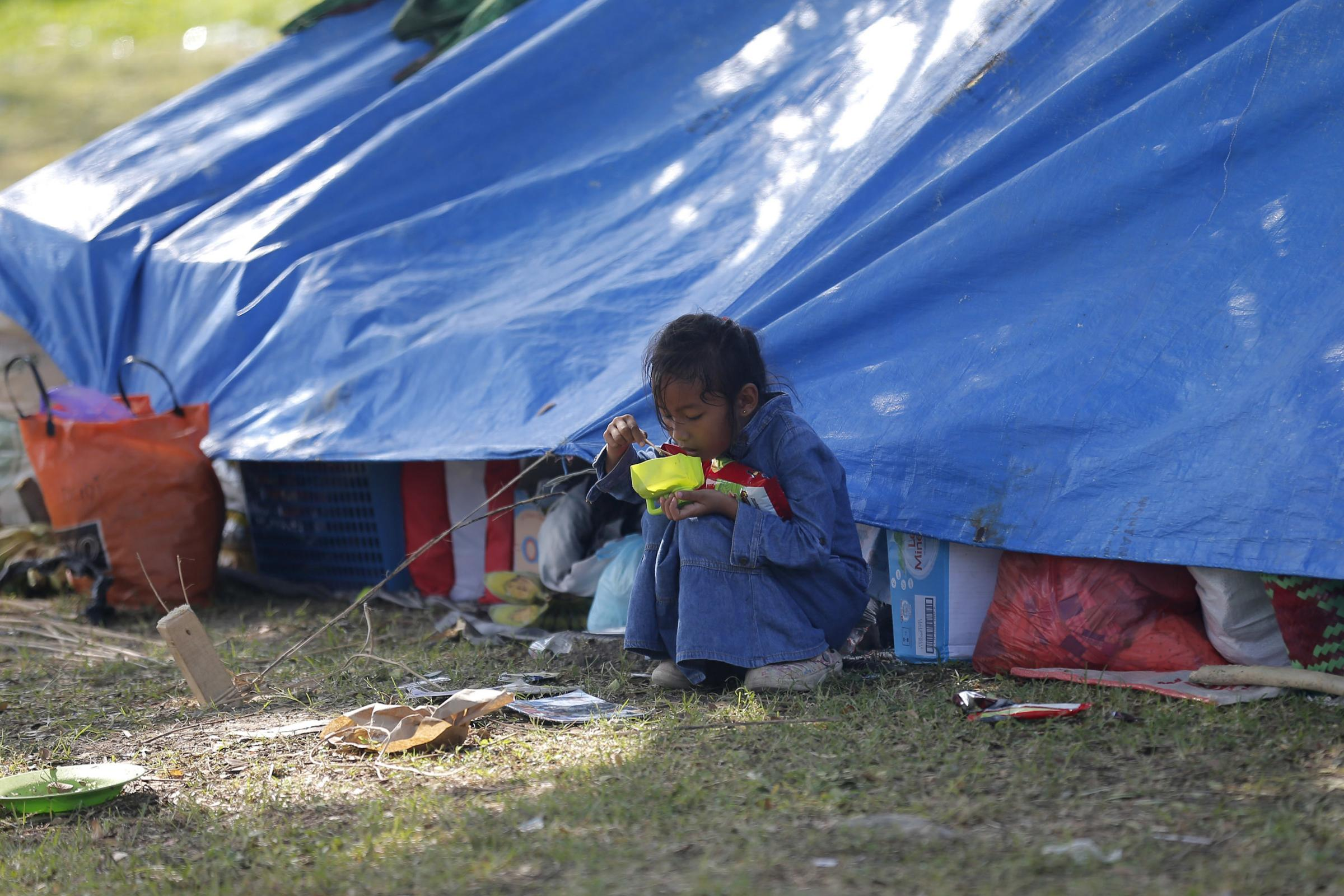 A child eats breakfast at a temporary shelter in Palu