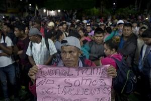"A Honduran migrant holds a sign that reads in Spanish ""Donald Trump. We are not delinquents."" as he, and hundreds of other migrants wait at the border between Guatemala and Mexico, in Tecun Uman, Guatemala, Friday, Oct. 19, 2018. Members of a 3,000-strong migrant caravan have massed in this Guatemalan border town across the muddy Suchiate River from Mexico, as U.S. President Donald Trump threatens retaliation if they continue toward the United States. (AP/Moises Castillo)"