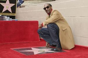 Rapper Snoop Dogg poses atop his new star on the Hollywood Walk of Fame following a ceremony in his honour in Los Angeles. (Photo by Willy Sanjuan/Invision/AP)