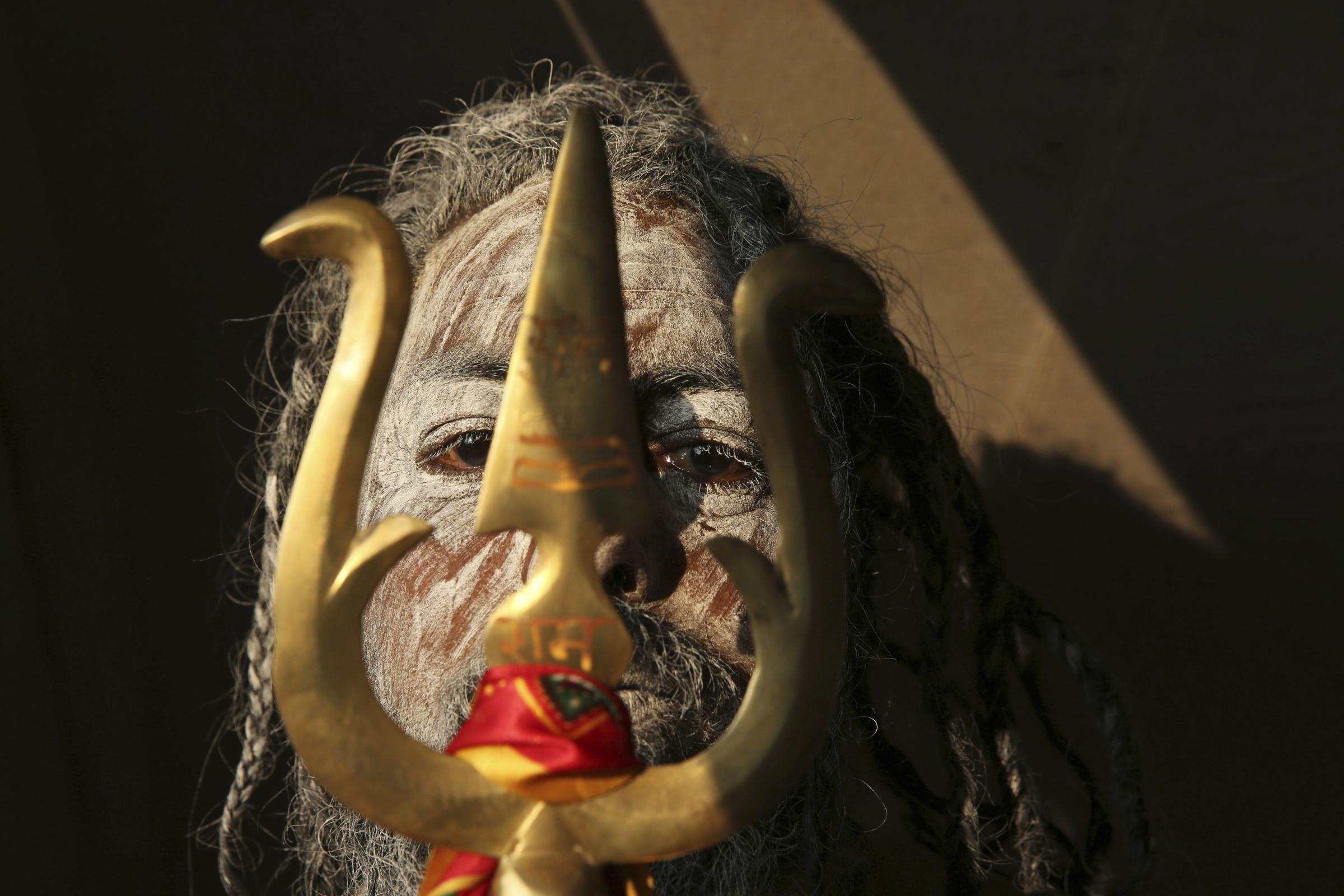 A Naga Sadhu stands with  trident as he participates in a procession towards the Sangam, the confluence of rivers Ganges and Yamuna. AP /Rajesh Kumar Singh).