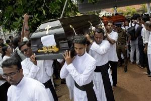Clergymen carry coffins for burial during a funeral service for Easter Sunday bomb blast victims at St. Sebastian Church in Negombo, Sri Lanka, Tuesday, April 23, 2019. (AP /Gemunu Amarasinghe)