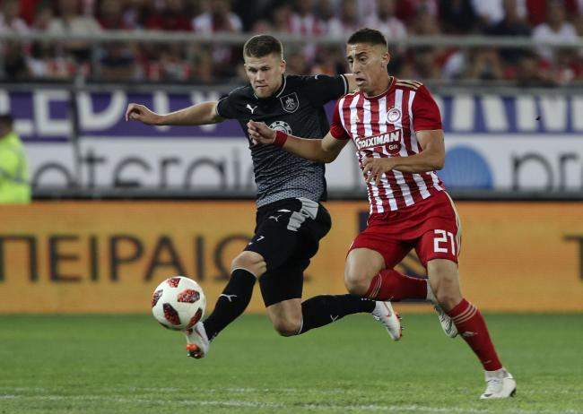 Olympiacos' Kostas Tsimikas, right, challenges for the ball with Burnley's Johann Gudmundsson during the Europa League playoffs, first leg, soccer match between Olympiacos Piraeus and Burnley at the Karaiskakis Stadium, in Athens, Greece, Thursday